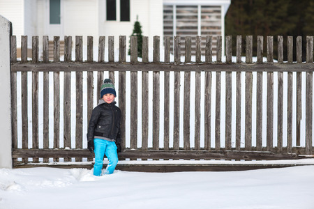 boy smiling: Beautiful cheerful boy is walking and playing in the winter park.