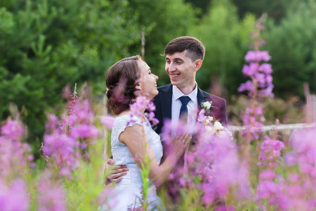 affable: Beautiful and happy bride and groom walking in summer forest. Young wedding couple.