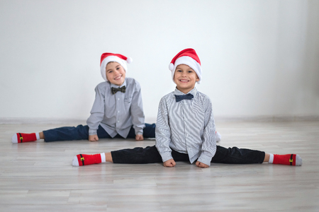 affable: Two boys brother sitting on the splits in Santa hat Stock Photo