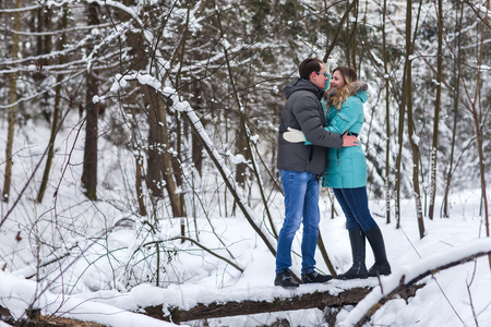 affable: Young beautiful couple walking in winter forest. Couple playing with snow in winter in a park.