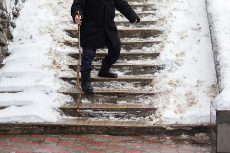 The old man down the stairs slippery in winter. Old man walking on ice.
