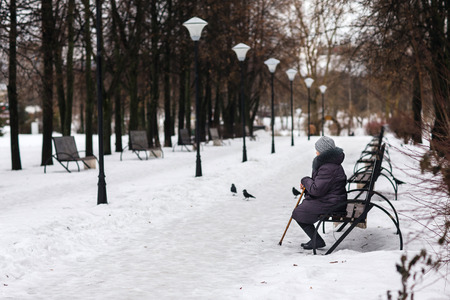 An old woman sitting on a bench in the park in winter.