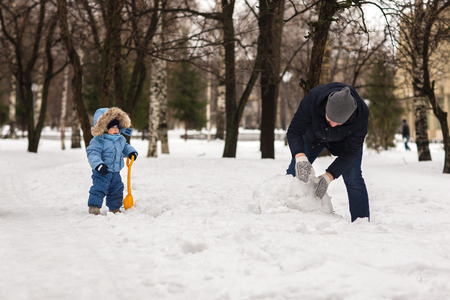 affable: Happy young dad walking with their baby in the park in winter and sculpts snowman.