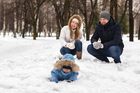 affable: Happy young family walking in a winter park. A family of three playing in the winter snow. Stock Photo
