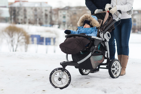 Happy young family walking in the park in winter. The parents carry the baby in a stroller through the snow. 스톡 콘텐츠