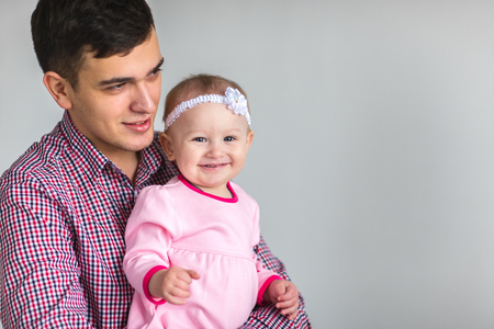 girlie: Young happy Dad keeps daughter in her arms.