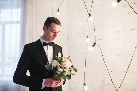 man in tuxedo: Handsome young groom in a tuxedo with a butterfly is holding a winter bridal bouquet. The man looks down and thinks, dreams, meditates on the wedding day.
