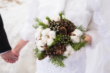 Beautiful winter wedding bouquet with cones, cotton and spruce branches. Bride holding a bridal bouquet. 스톡 콘텐츠