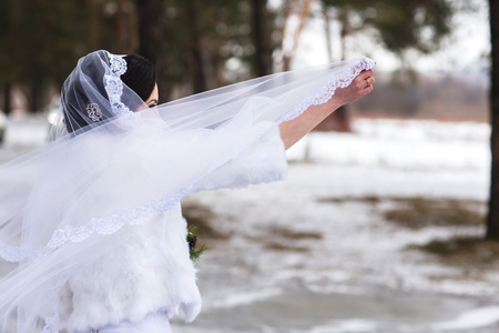 glory of the snow: Beautiful young bride holding a gorgeous white wedding veil. Luxury Veil developing the wind.