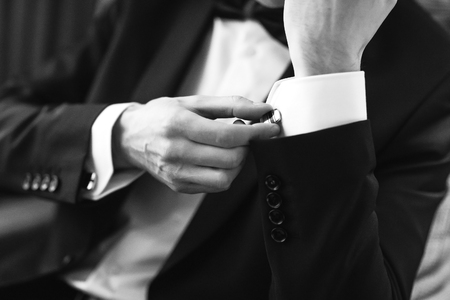 Confident man buttons cufflinks. Cufflinks closeup. Men's suit, tuxedo. Archivio Fotografico
