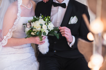 wedding party: Beautiful winter wedding bouquet. Bridal bouquet with cones, cotton and spruce branches. The bride holds a wedding bouquet next to the groom.