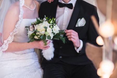 Schöne Winter Hochzeit Bouquet. Brautstrauß mit Zapfen, Baumwolle und Fichtenzweigen. Die Braut hält eine Hochzeit Bouquet neben dem Bräutigam. Standard-Bild