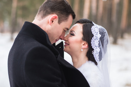 snow man party: Young couple newlyweds walking in a winter forest in the snow. Bride and groom hugging in the park in winter. Beautiful man and woman in their wedding clothes are among the pines.