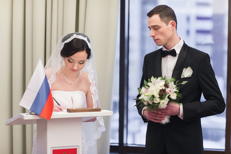affable: Bride and groom on marriage registration. The groom looks at the bride. Newlyweds at the wedding ceremony.