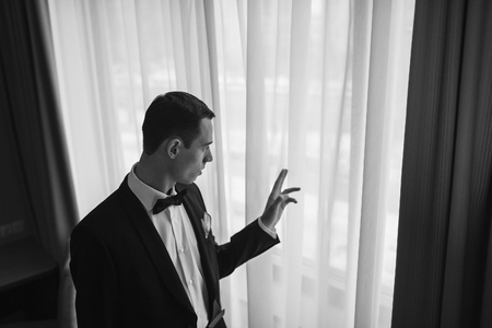 luxury apartment: A man in a tuxedo looking out the window. Groom before the wedding the bride is thinking about. Confident man dreams and worries.