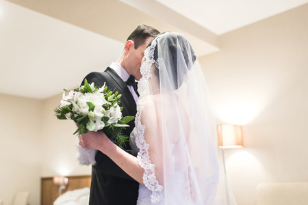 The first meeting of the bride and groom on the wedding day. Emotions newlyweds before the wedding ceremony. Bride and groom look at each other, hugging and kissing.