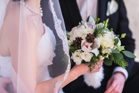 Beautiful winter wedding bouquet. Bridal bouquet with cones, cotton and spruce branches. The bride holds a wedding bouquet next to the groom.