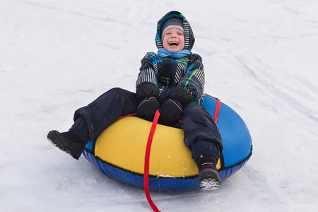 Cheerful handsome boy riding a roller coaster. Toddler walking in the snow in winter. The child laughs and smiles in winter park. Stok Fotoğraf
