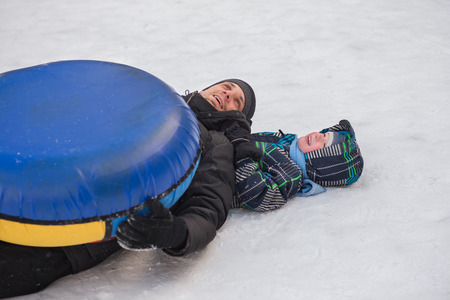 affable: A young man with a cheerful boy with a roller coaster ride in the winter on the ice. Handsome Dad and son laughing in a winter park. Happy family playing with snow. Stock Photo