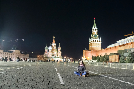 affable: Beautiful woman walking on the area. A young girl sits on Red Square in Moscow. Attractive woman dreaming and looking forward.