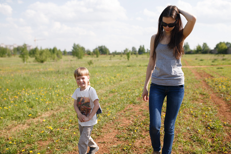 affable: Young beautiful mother with her son walking on the field in summer. Bright sunny day. Woman and child go and laugh.