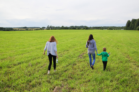affable: Young beautiful mother walking on the field in summer with her son and daughter. Young family walking vecherm years. People go forward into the distance.