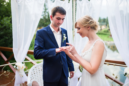 fingers put together: Bride and groom exchange wedding rings and wear at the ceremony. Stock Photo