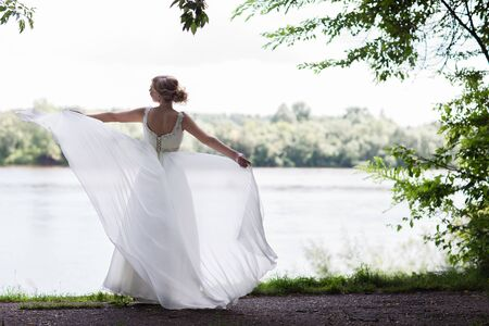 bride dress: Young beautiful bride plays a wedding dress. Dress develops in the wind. Happy bride in a wedding dress is spinning. Stock Photo