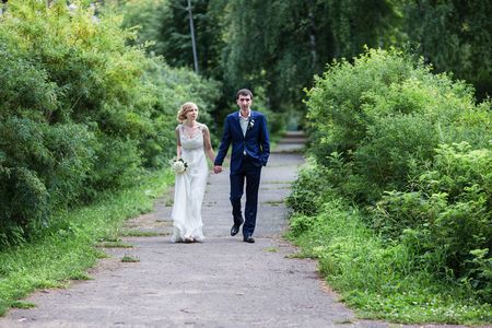 newly married: A happy young newly married couple walking in the park. Beautiful bride and groom kissing in the woods. Stock Photo