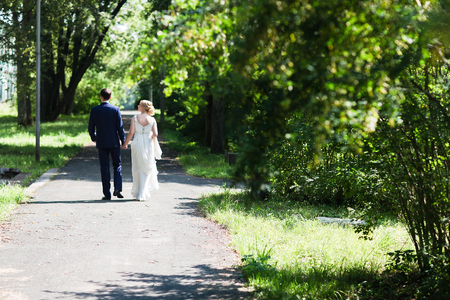 newly married couple: A happy young newly married couple walking in the park. Beautiful bride and groom kissing in the woods. Stock Photo