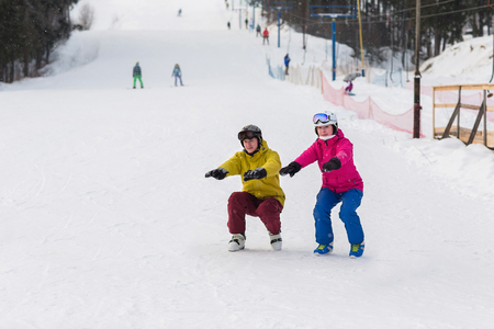 crouch: Snowboarders and skiers do warm up before exercise. Athletes crouch on the slope in winter.