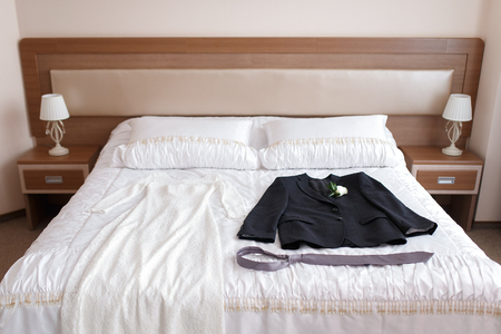 strapless: Wedding dress and suit lying on a bed in a hotel room. Stock Photo