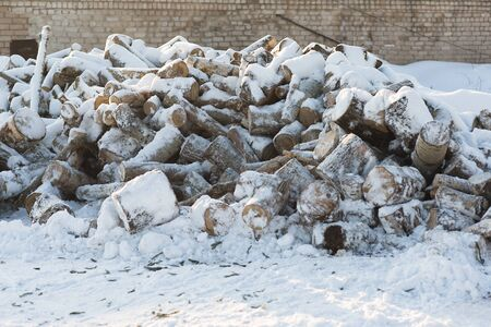 heaped: Firewood lie heaped in the snow in winter.
