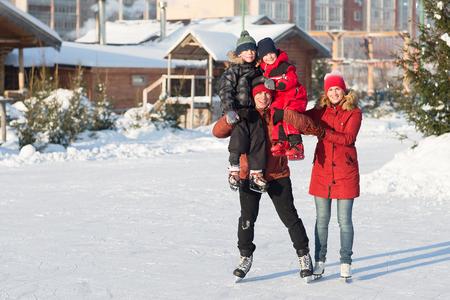 mujeres y niños: patín feliz familia joven en la pista en el invierno. Hermosa familia caminando y jugando sobre el hielo en invierno. Foto de archivo