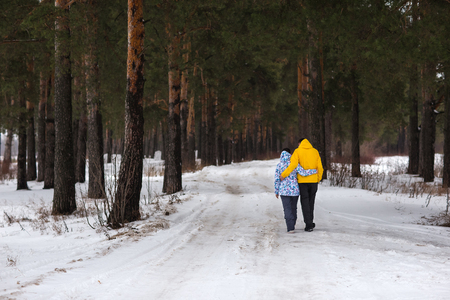 glory of the snow: Young beautiful couple walking in winter forest. Lovers playing with snow. Stock Photo