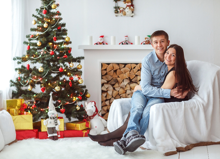 affable: Young beautiful couple playing near a Christmas tree. Loving couple sitting by the fireplace.