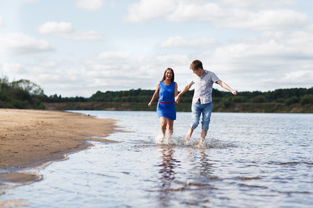 affable: Young beautiful couple walking along the beach near the river. Stock Photo
