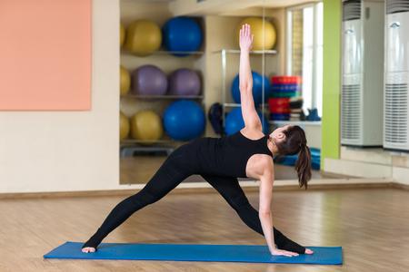 introversion: Woman Yoga Parivrtta Trikonasana - Revolved Triangle Pose in the fitness and gym. Stock Photo
