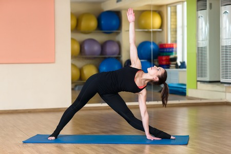 revolved: Woman Yoga Parivrtta Trikonasana - Revolved Triangle Pose in the fitness and gym. Stock Photo