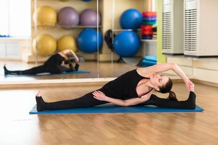 konasana: Young sports woman practicing yoga Upavistha Konasana Wide Seated Forward Bend Pose. Indoor gym.