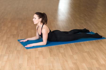 bhujangasana: Young athletic woman doing yoga pose in bhanga Asana, Cobra Pose. Indoor gym.