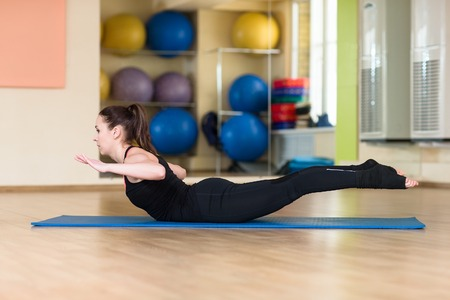 serpiente cobra: Young athletic woman doing yoga pose in bhanga Asana, Cobra Pose. Indoor gym.