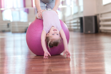 position d amour: Mom is doing exercises gymnastics coach with a daughter in the gym.