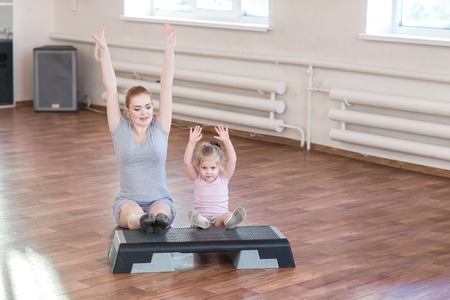 mum and child: Pregnant woman with her first kid daughter doing gymnastics in living room. Stock Photo