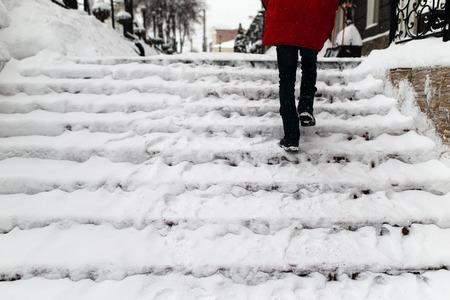 mujer sube las escaleras en la nieve Foto de archivo