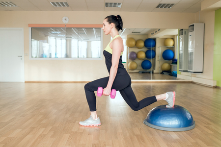 hemisphere: Beautiful young woman doing fitness in the gym. Girl uses fitball exercise, expander, hemisphere. Stock Photo