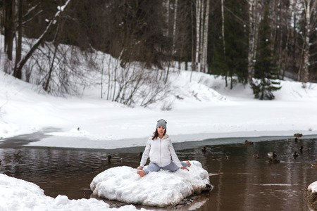 girl in sportswear: Young athletic woman doing yoga in the woods in winter. Beautiful girl engaged in fitness in winter park. barefoot in the snow.