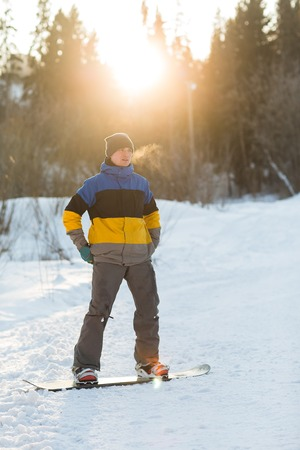 ski walking: Male snowboarder walking in a winter day on the hill in the woods. Portrait of a snowboarder in the mountains in winter on the ski slope. Stock Photo