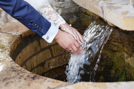 newly wedded couple: Wedding hands. Hands of newly wedded with wedding rings on their fingers under running water Stock Photo