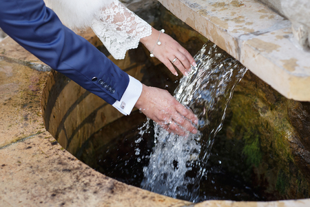 newly: Wedding hands. Hands of newly wedded with wedding rings on their fingers under running water Stock Photo
